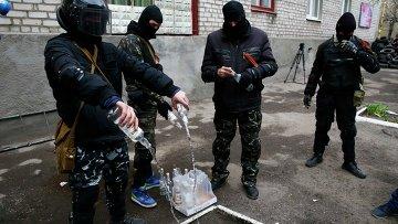 Люди в масках используют пустые бутылки водки для бензиновых бомб в Славянске