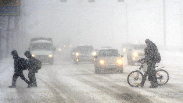 Пешеходы переходят дорогу во время сильного снегопада. Архивное фото