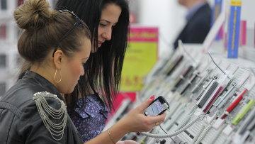 Девушки выбирают мобильный телефон в магазине. Архивное фото