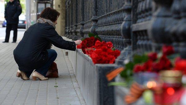 Люди возлагают цветы к зданию посольства Украины в Москве в память о погибших в результате военных столкновений