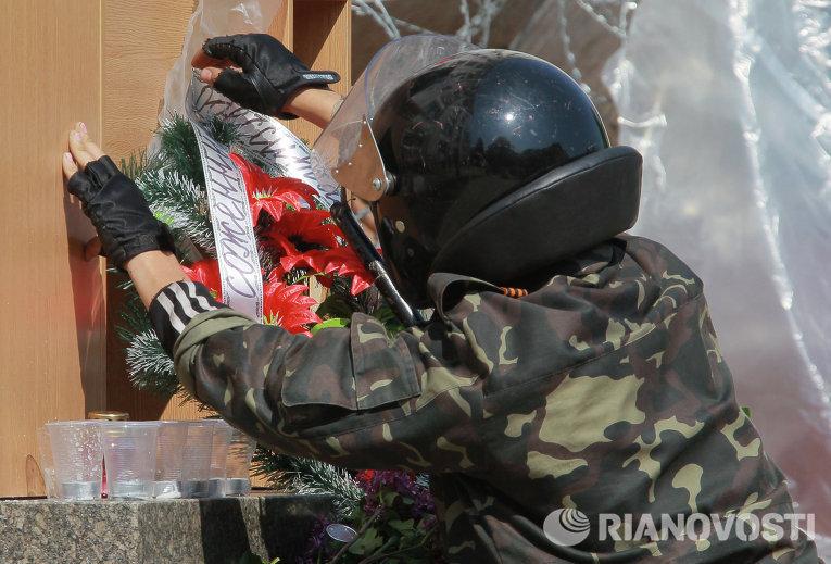 Участник народного ополчения поправляет ленточку на венке в память о жертвах в Одессе перед зданием областной администрации