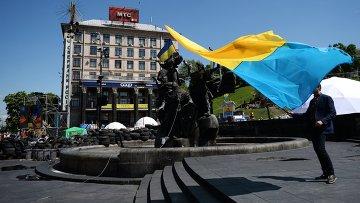 Молодой человек с украинским флагом у памятника основателям Киева на площади Независимости. Архивное фото