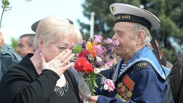 Жительница Украины поздравляет ветерана Великой Отечественной войны на праздничных мероприятиях, посвященных 9 мая. Архивное фото