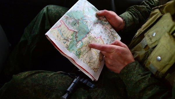 Доброволец народного ополчения смотрит карту Луганской области