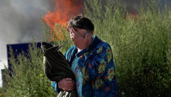 Женщина плачет возле своего горящего дома в Славянске