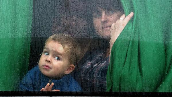 Женщина с ребенком в автобусе с беженцами, архивное фото