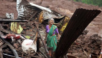 Женщина ищет выживших после оползня родственников в Индии