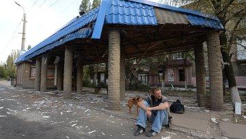 Мужчина сидит возле разрушенной остановки в Горловке