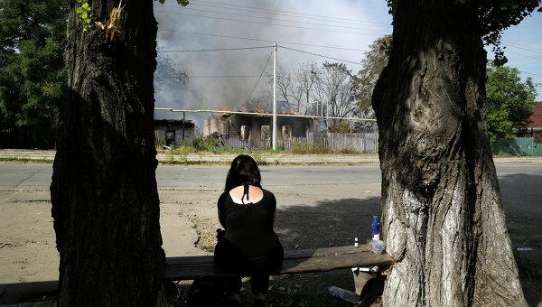 Женщина сидит напротив своего дома сгоревшего в результате обстрела в Донецке