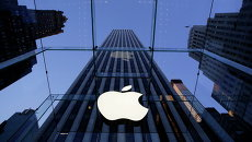 Логотип компании Apple над входом в здание в Нью-Йорке, США