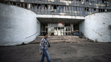 Житель Луганска проходит мимо здания, поврежденного артобстрелом. Архивное фото