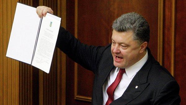 Президент Украины Петр Порошенко показывает подписанное соглашение об ассоциаци с ЕС