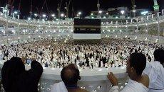 Мусульманские паломники совершают молитву возле Каабы, святыни в виде кубической постройки во внутреннем дворе мечети Масджид аль-Харам в Мекке, Саудовская Аравия