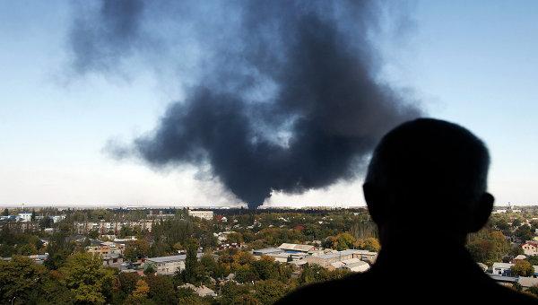 Житель города смотрит на дым над Донецком