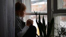Девочка сидит у окна в детском доме. Архивное фото