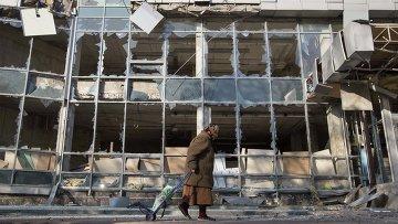 Женщина на фоне разрушенного в результате обстрела здания в Донецке, Украина. 15 октября 2014