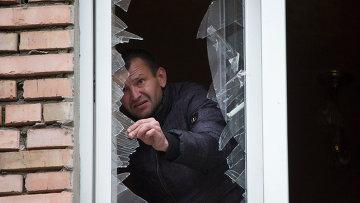 Мужчина убирает осколки от разбитого окна после обстрела Донецка. Архивное фото