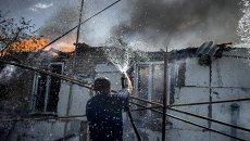 Мужчина тушит пожар в станице Луганская после авиаудара. Архивное фото