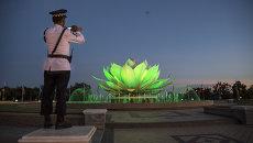 Полицейский на посту снимает на мобильный телефон фонтан в виде цветка лотоса в Нейпьидо, Мьянма