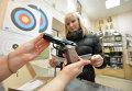 Покупательница рассматривает образцы оружия