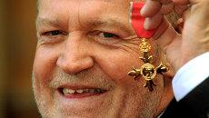 Британский музыкант Джо Кокер позирует фотографам с орденом Британской империи за вклад в историю музыки