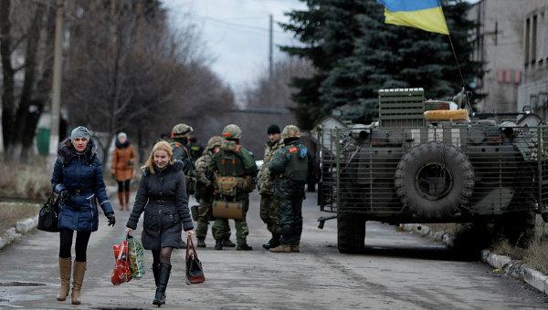Местные жители проходят мимо солдат украинской армии в селе Дебальцево, Донецкая область