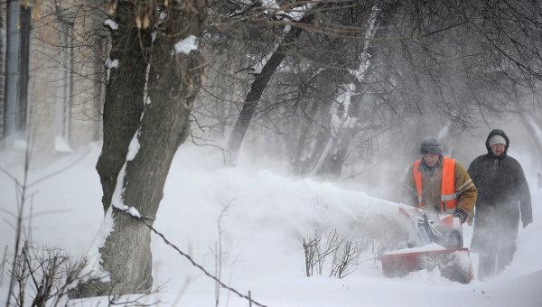 Сотрудник служб ЖКХ очищает двор от снега, Украина. Архивное фото