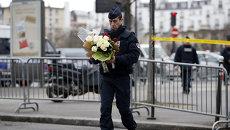 Полицейский несет цветы к месту нападения на кошерный магазин в Париже. Архивное фото