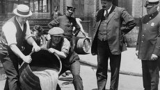 Инспекторы сливают баррель конфискованного пива в канализацию во время действия сухого закона в Америке