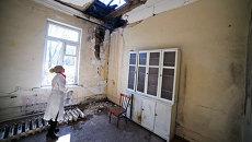 Сотрудница осматривает повреждения после обстрела в городской больнице № 20 в Донецке