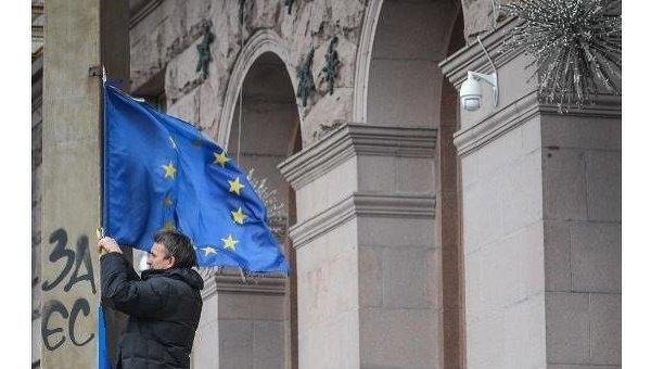 Участник акций за евроинтеграцию Украины закрепляет флаг ЕС