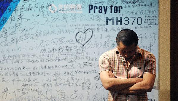 Мужчина стоит на фоне стенда, посвященного пассажирам пропавшего рейса MH370 компании Malaysia Airlines