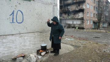 Жительница города Дебальцево готовит еду на костре на улице у жилого многоквартирного дома, пострадавшего в результате обстрелов во время боевых действий. Архивное фото