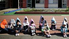 Школьники во время учений на случай землетрясения в Токио. 11 марта 2015