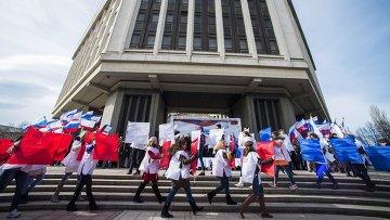 Участники торжественного митинга по случаю празднования годовщины Крымской весны на площади у Государственного Совета РК в городе Симферополе