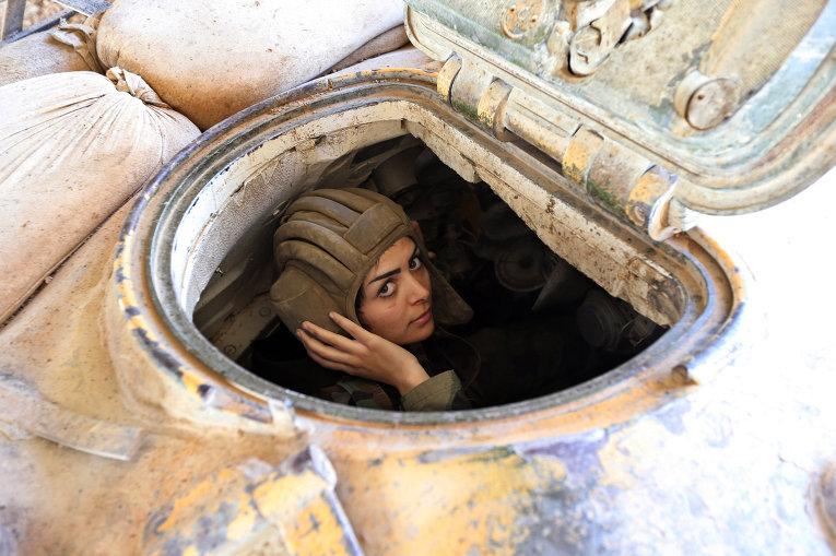 Женщина-военный сирийской армии управляет танком во время столкновений в восточной части Дамаска