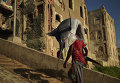 Человек несет рыбу-парусник на улице Могадишо