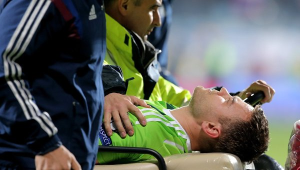 Работники медицинской службы уносят с поля вратаря сборной России Игоря Акинфеева, получившего травму в матче отборочного турнира чемпионата Европы 2016 между сборными Черногории и России.
