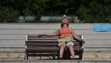 Женщина загорает на скамейке