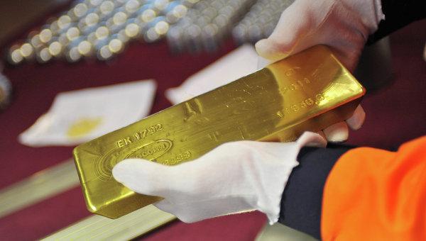 Золотой слиток в руках рабочего. Архивное фото