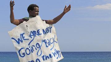 Мигрант держит плакат с надписью Мы не собираемся обратно на границе Франции и Италии в городе Вентимилья