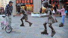 Девушка фотографируется у скульптурной группы на одной из улиц Маньчжурии