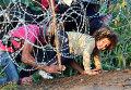 Мигранты проползают под колючей проволокой на Венгерско-Сербской границе