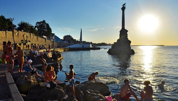 Отдыхающие и местные жители купаются у памятника затопленным кораблям на закате недалеко от Приморского бульвара в Севастополе