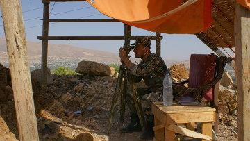 Сирийский военный ведет наблюдение за позициями исламистов в окрестностях города Эз-Забадани, Сирия