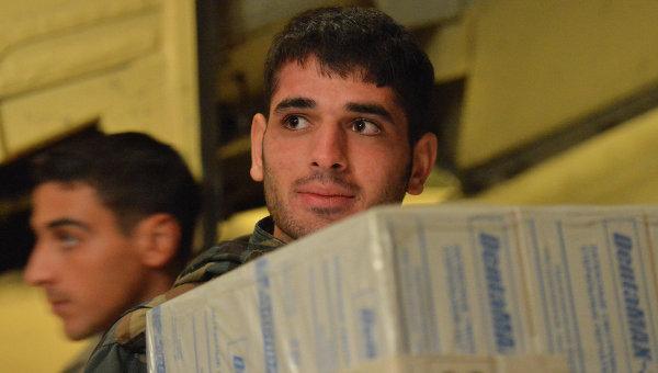 Сирийские военнослужащие разгружают коробки с гуманитарной помощью из России. Архивное фото