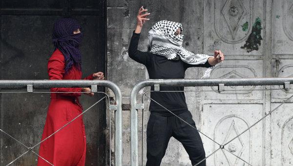 Молодая женщина из Палестины бросает камни в сторону израильских сил безопасности во время столкновений