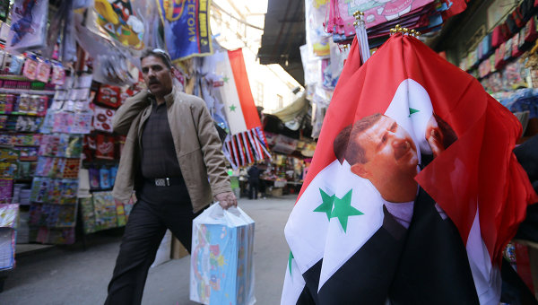 Флаг Сирии с изображением президента Сирии Башара Асада на рынке в Дамаске. Сирия, ноябрь 2015