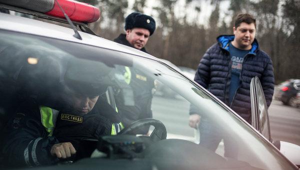 Сотрудник ГИБДД проверяет документы у водителя. Архивное фото