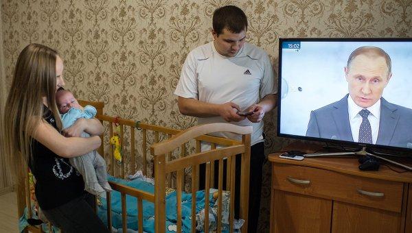 Молодая семья в Омске смотрит телевизионную трансляцию послания президента РФ Владимира Путина к Федеральному Собранию